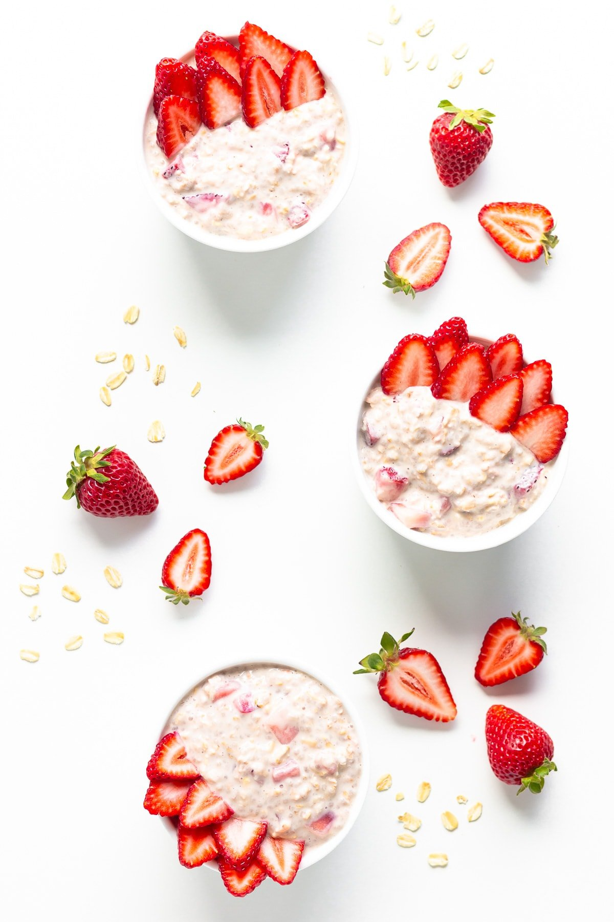 Three bowls of strawberry overnight oats on a white background garnished with fresh strawberries.