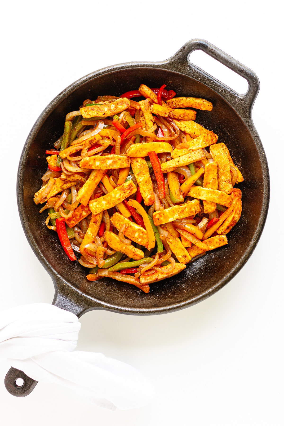 Fajita veggies with pan fried halloumi strips in a cast iron skillet.