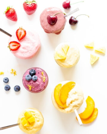 Overhead image of six different flavors of blender ice cream in jars with fruit garnishes.