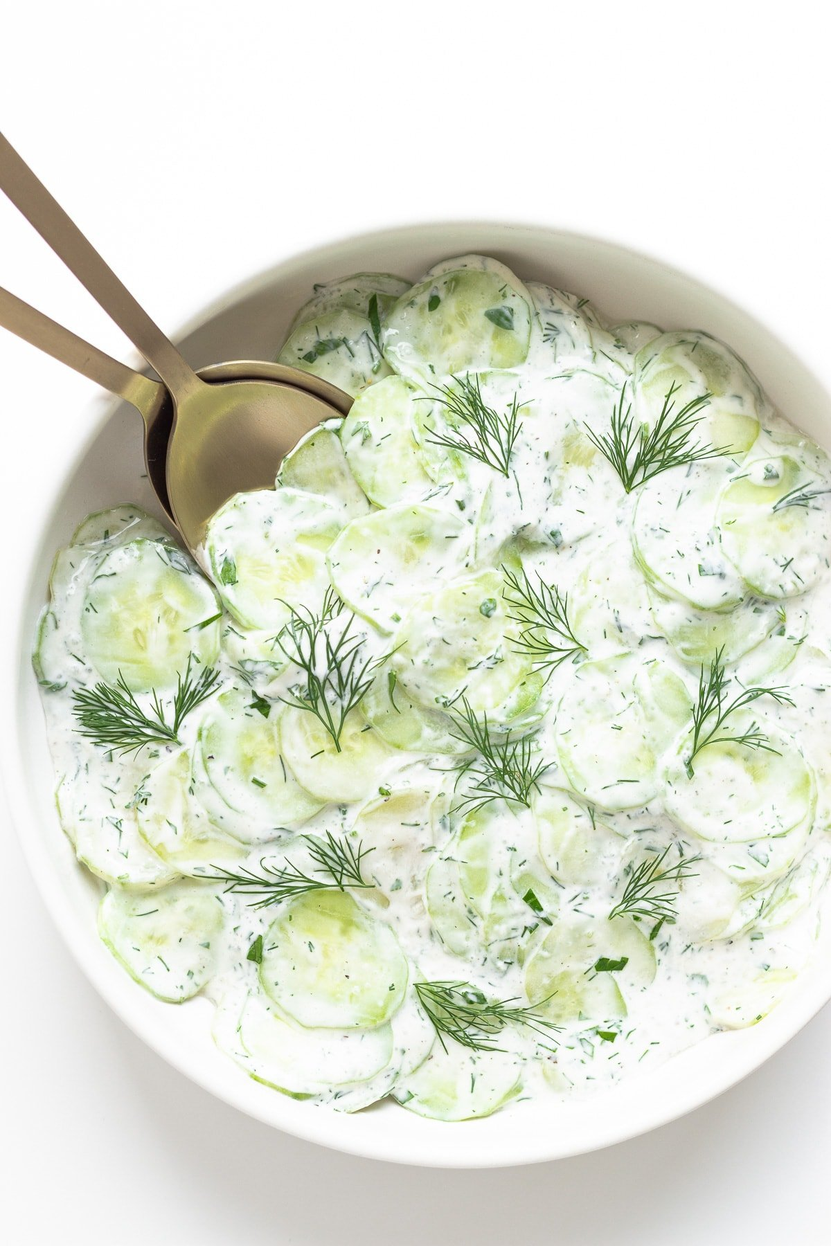 Sour cream cucumber salad in a white bowl with gold salad servers.