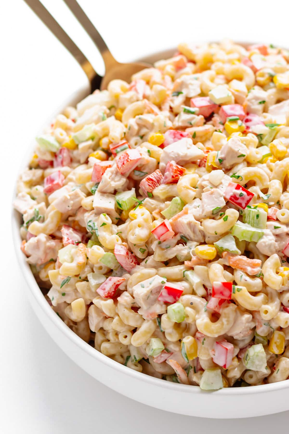 Chicken macaroni salad in a large white serving bowl with gold servers sticking out.