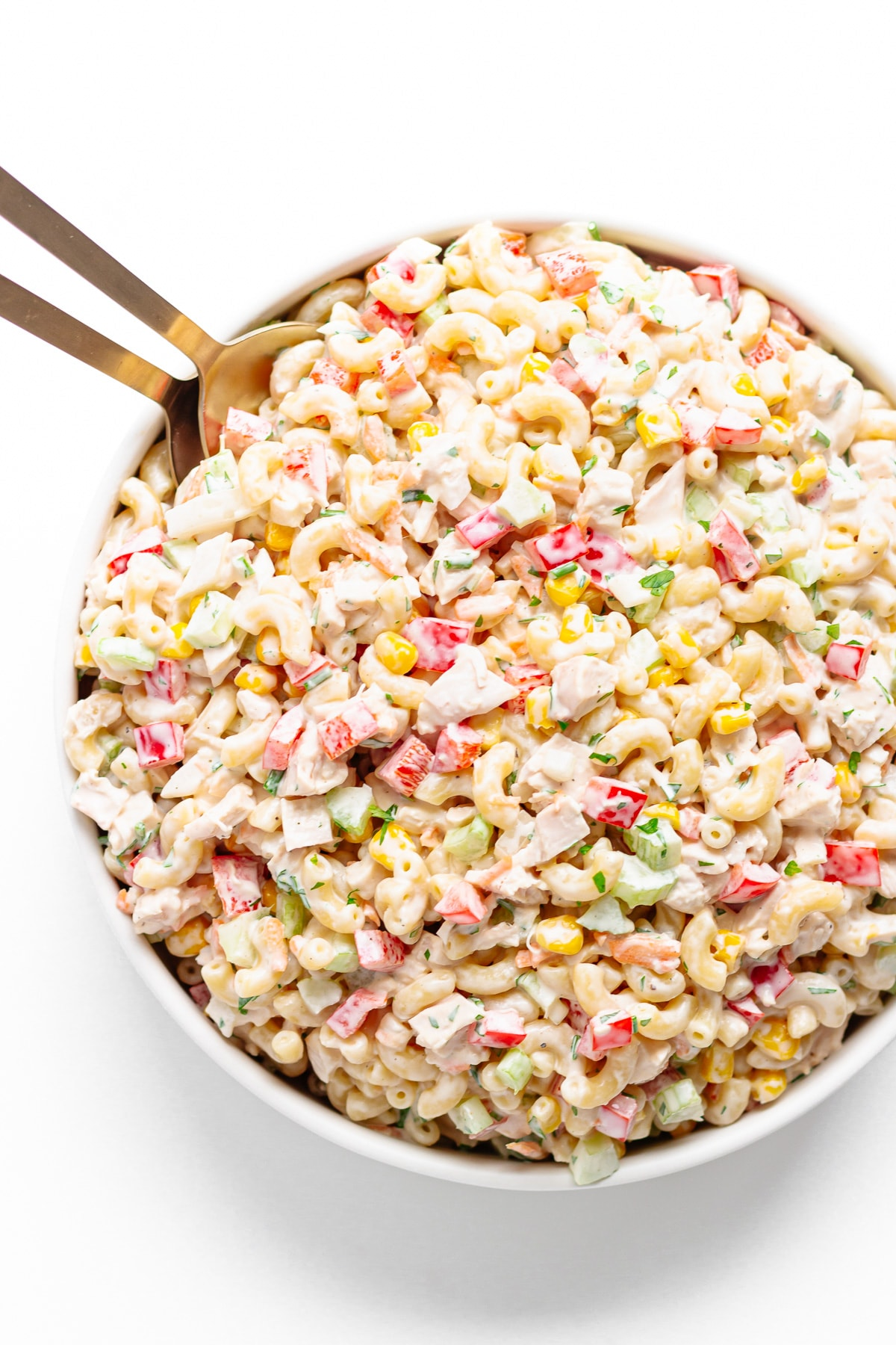 Large white serving bowl of creamy chicken pasta salad with gold servers tucked into corner.