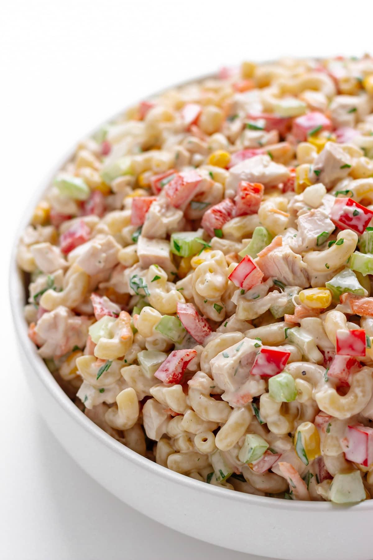 White serving bowl filled with macaroni salad.