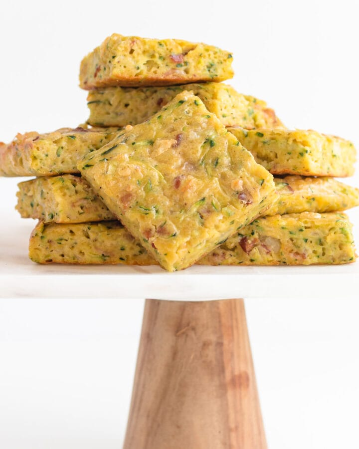 Pile of zucchini slice on a marble and wood cake stand.